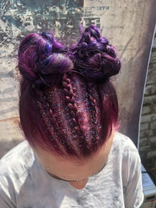 A woman with a glittery purple unicorn braid and space bun hairstyle.